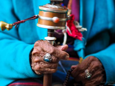 Praying wheel in hands of old tibetian woman, Nepal